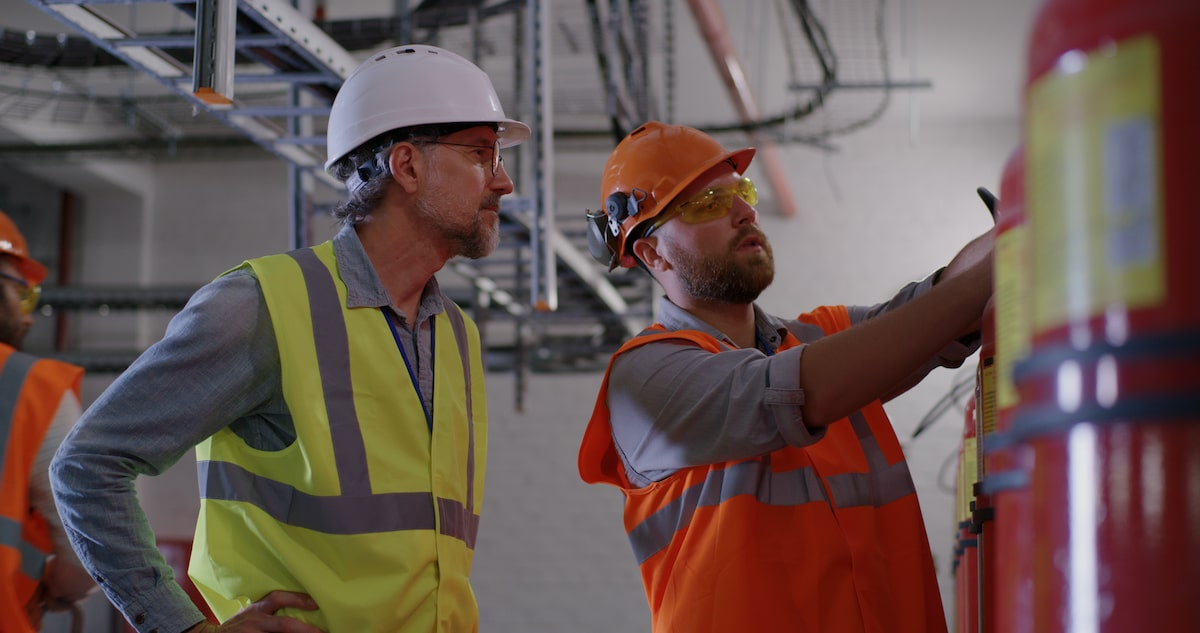 Bearded worker demonstrating fire extinguishers to mature inspector while working on power station